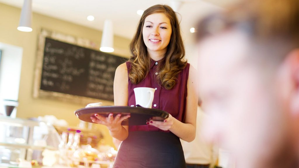 Eine Jugendliche beim Nebenjob im Café.