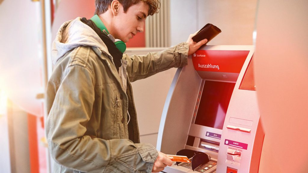 Ein Jugendlicher hebt am Geldautomaten mit seiner Karte Geld vom Taschengeldkonto ab.