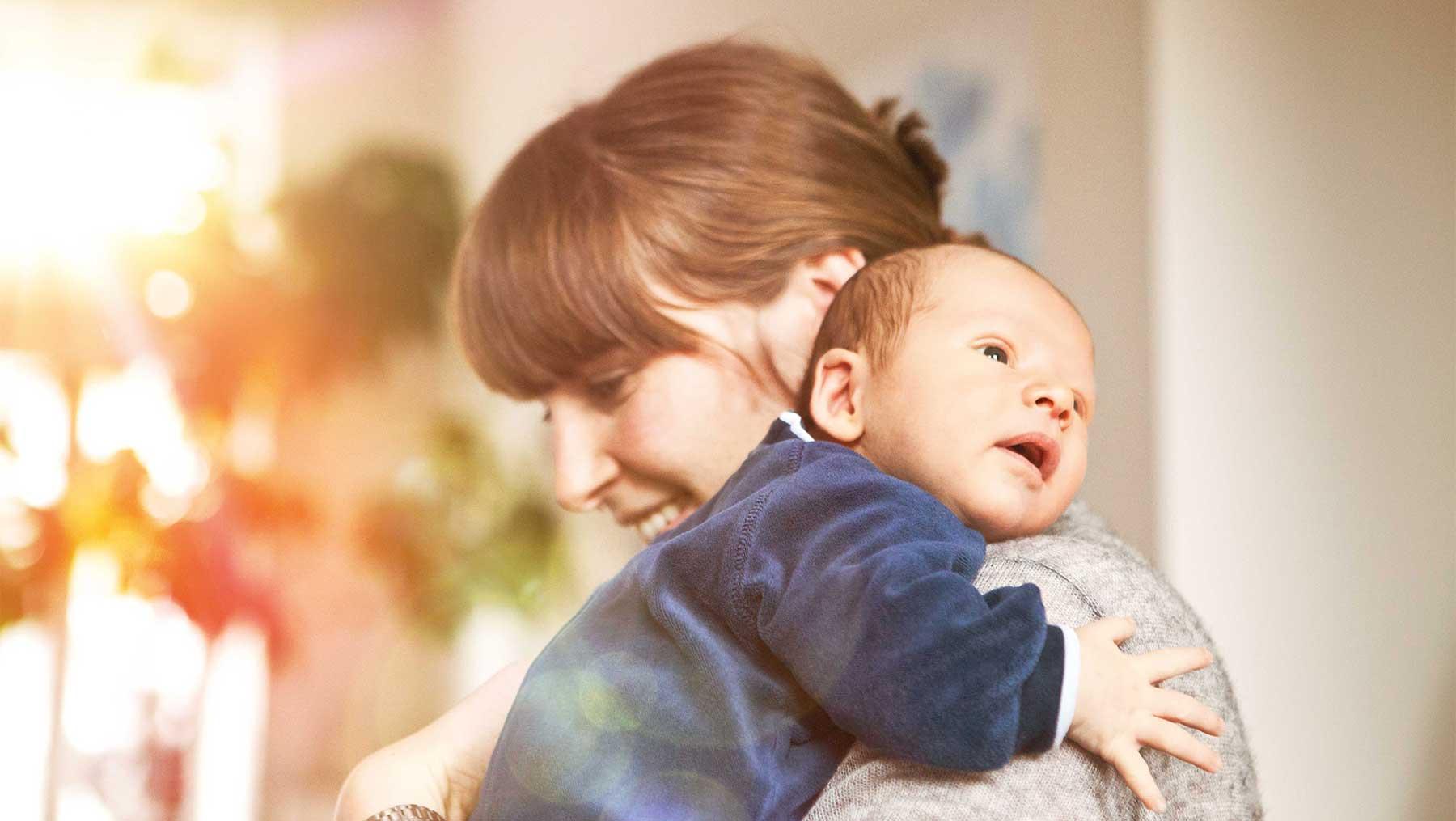 Eine Mutter hält ihren Neugeborenen auf dem Arm.