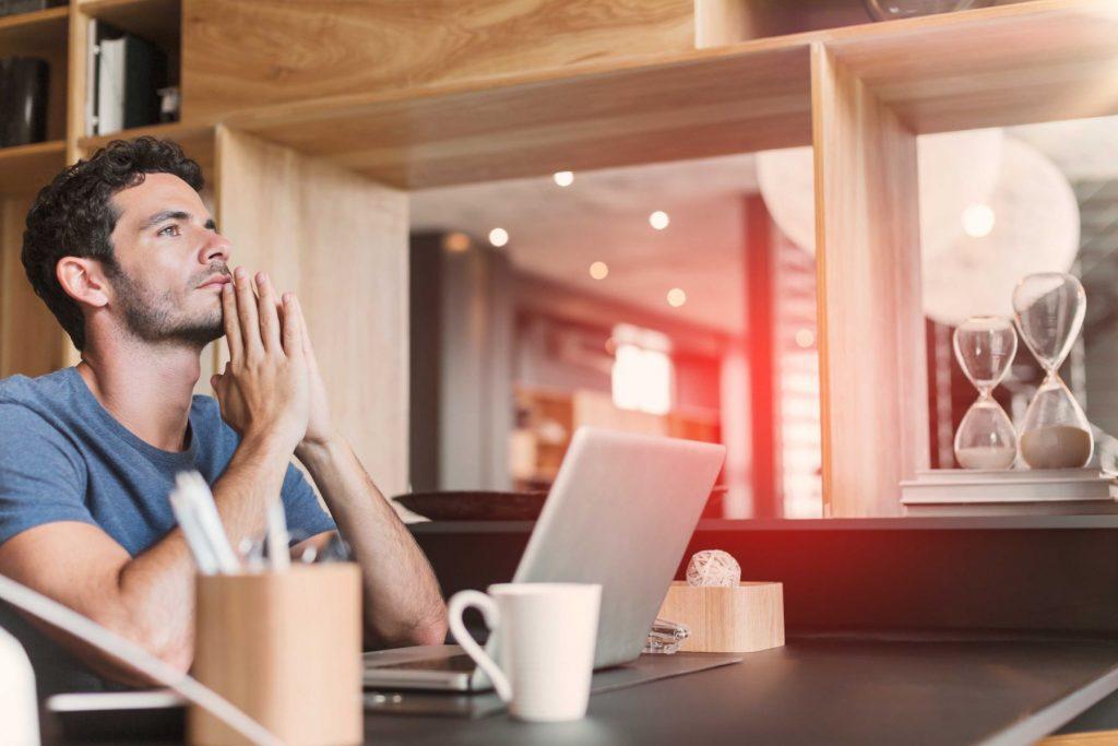 Ein Mann sitzt vor seinem Laptop und denkt über seine finanzielle Situation nach.